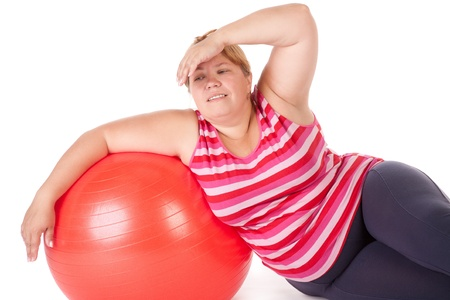 overweight people: tired fat woman with big red gymnastic ball Stock Photo