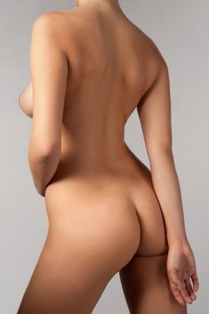 seins nus: Portrait de belle femme sur un fond gris Banque d'images