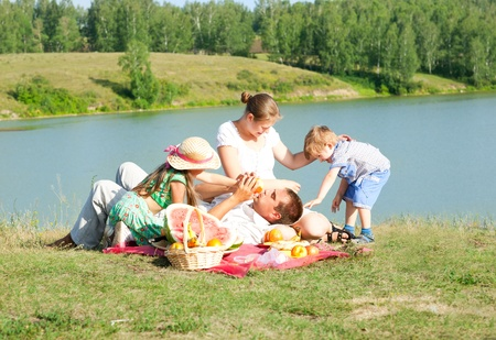 family resting on the lake photo