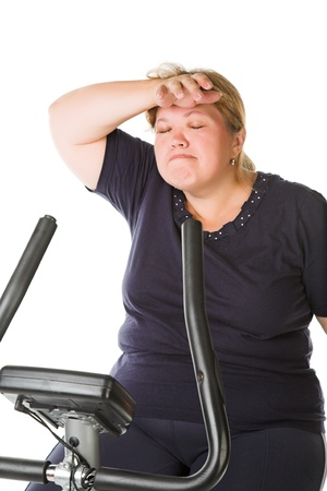 tired fat woman training on the bike photo