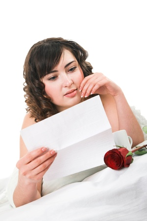 young woman reading letter and holding rose  photo