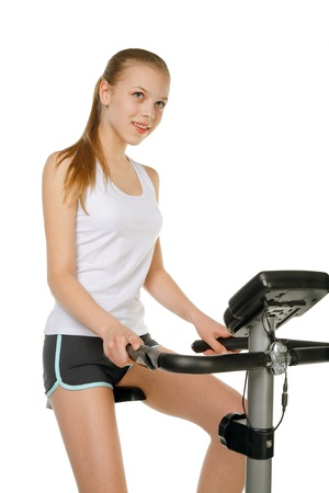 beauty girl with gym bicycle machine photo