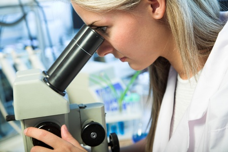 beauty researcher looking through microscope in laboratory Stock Photo