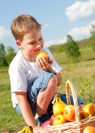 happy boy with apples resting outdoor photo