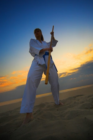 young woman training karate on sunset beach photo