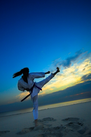 young woman training karate on sunset beach photo