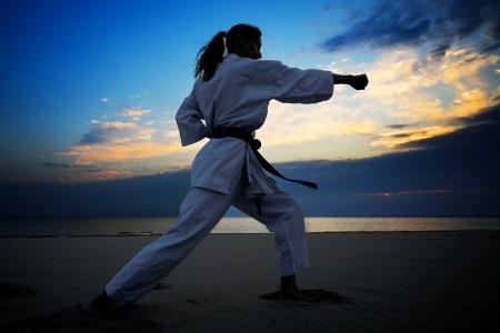 karate: young woman training karate on sunset beach Stock Photo