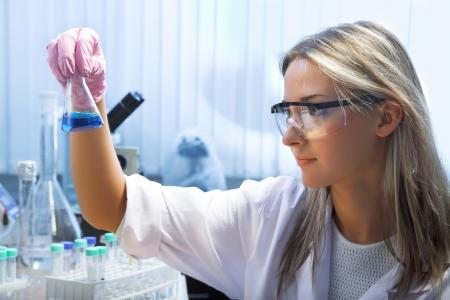 female researcher look at retort with blue liquid