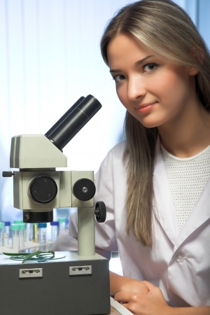 researcher: beauty researcher looking through microscope in laboratory Stock Photo