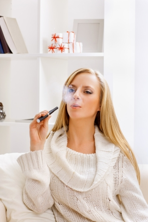 young beauty girl with e-cigarette  in light room  photo