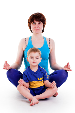 mother and son doing yoga. isolated on white photo