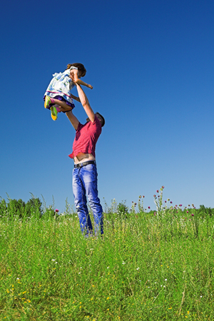 raise your hand: Happy family rest on the summer meadow, father fun throws up daughter in the air.