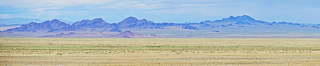 Mongolian dry steppe and rocky mountains on the horizon. Panorama