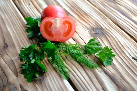 tomatoes and greens on a wooden table