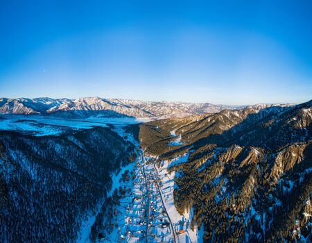 Winter village in the valley of the river between the mountains. Aerial pano, Siberia, Altay mountain.