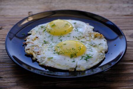 Fried Eggs on a plate (wooden background)  Stok Fotoğraf