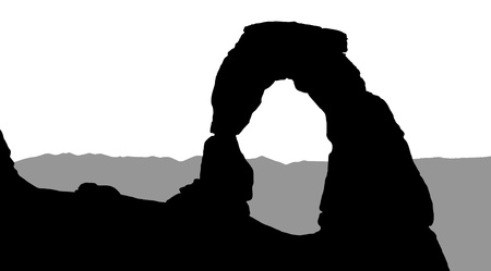 Silhouette of Delicate Arch with mountains in the background