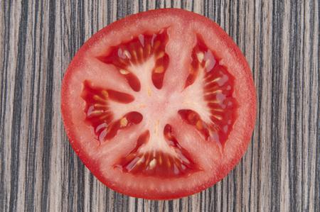 Slice tomato on wooden background 版權商用圖片