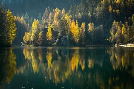 Autumn trees reflected on still black lake