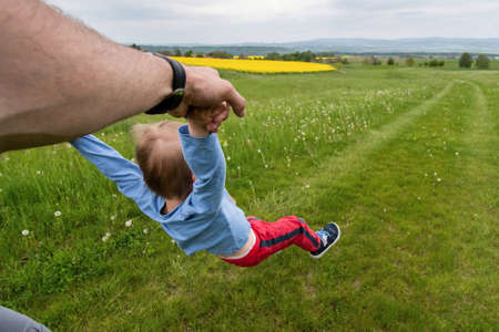 little child swings in the hands of parents on a meadow with a view