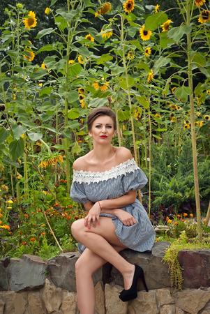 beautiful girl near sunflowers in a short dress in summer