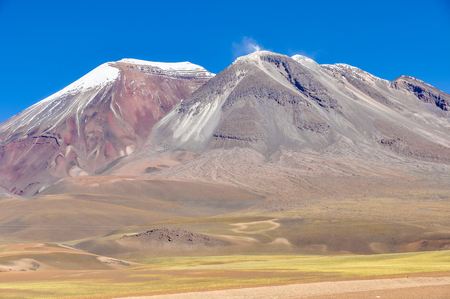 high plateau: Colorful volcano emitting smoke in the high Andean plateau in Bolivia Stock Photo