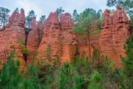 ochre: Reddish rock formations made of ochre near the hilltop village of Rousillon, Provence, France