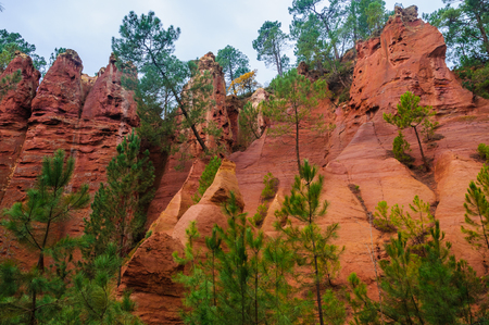 hilltop: Reddish rock formations made of ochre near the hilltop village of Rousillon, Provence, France
