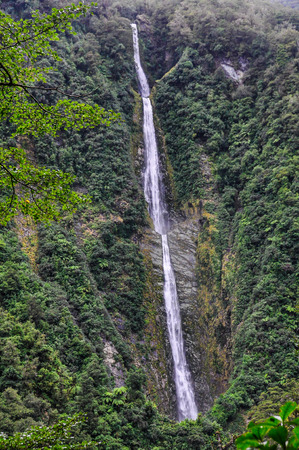 Tall waterfall on the Milford Road in the Southern Island of New Zealand