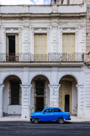 paseo: Blue car parking in front of old buildings in Paseo de Marti in Havana, the capital of Cuba