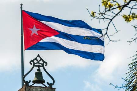 cuban flag: Cuban flag moving on top of a church in Plaza de las Armas square in Havana, Cuba