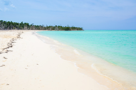 Alone on a secluded white sand beach in the tropical Cayo Levisa Island in Cuba