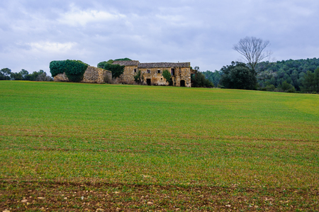 Abandoned country house and green fields in the countryside of Catalonia, SPain