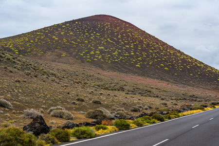 Road near volcanic crater in Timanfaya National Park, Lanzarote, Spain