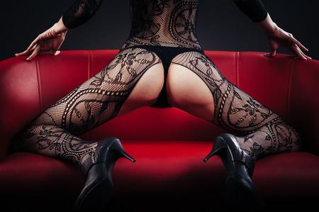 Сексуальная красивая обнаженная женщина в черном эротическом белье на черном фоне
