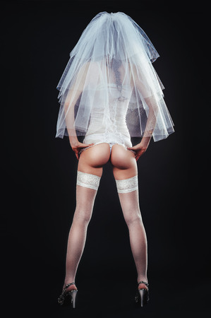 nude bride: Sexy beautiful nude bride with veil in white erotic lingerie on a black background. beauty nude portrait of bride