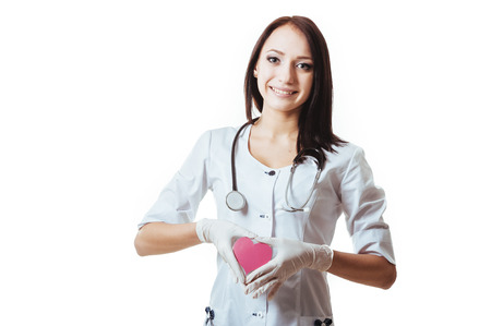 Positive female doctor standing with stethoscope and red heart symbol isolated on white background. photo