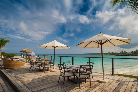 Outdoor restaurant at the beach. Cafe on the beach, ocean and sky. Table setting at tropical beach restaurant. Dominican Republic, Seychelles, Caribbean, Bahamas. Relaxing on remote Paradise beach. photo