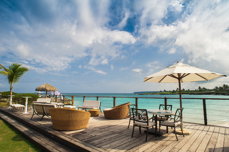 hotel exterior: Outdoor restaurant at the beach. Cafe on the beach, ocean and sky. Table setting at tropical beach restaurant. Dominican Republic, Seychelles, Caribbean, Bahamas. Relaxing on remote Paradise beach. Stock Photo