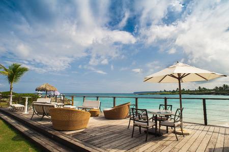 Outdoor restaurant at the beach. Cafe on the beach, ocean and sky. Table setting at tropical beach restaurant. Dominican Republic, Seychelles, Caribbean, Bahamas. Relaxing on remote Paradise beach. Standard-Bild