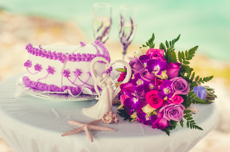 Decorative glass of champagne, wedding cake and bridal bouquet on a decoration table against a tropical caribbean beach, Dominican Republic. Fantastic dinner sweets near the sea on wedding day. photo