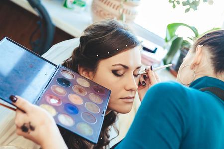 bridal salon: Woman applying make up for a bride in her wedding day near mirror. Closeup of a makeup artist applying makeup