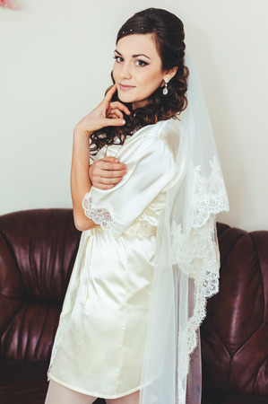 foretaste: bride tries on a wedding dress dressing gown. Happy beautiful bride with Bridal Hairstyle wedding makeup, newlywed blond girl in peignoir waiting for groom. Happy bride have final preparation for wedding. Beautiful newlywed woman with long hair
