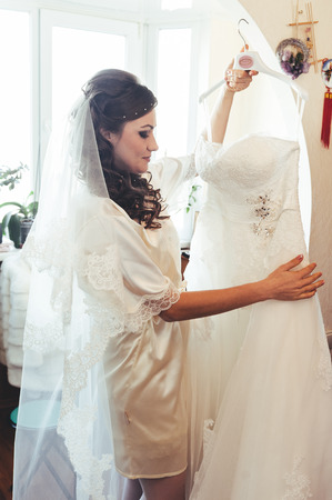 bride tries on a wedding dress dressing gown. Happy beautiful bride with Bridal Hairstyle wedding makeup, newlywed blond girl in peignoir waiting for groom. Happy bride have final preparation for wedding. Beautiful newlywed woman with long hair