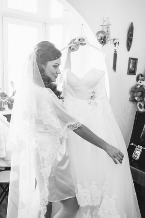 peignoir: bride tries on a wedding dress dressing gown. Happy beautiful bride with Bridal Hairstyle wedding makeup, newlywed blond girl in peignoir waiting for groom. Happy bride have final preparation for wedding. Beautiful newlywed woman with long hair