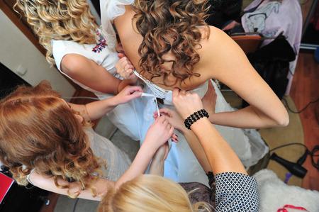 bridesmaid: Bridesmaid is helping the bride to dress. bridesmaid tying bow on wedding dress.