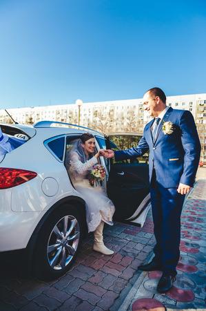 Bride and groom near vintage car on wedding day photo