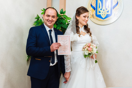 marriage certificate: The marriage register. Bride and Groom Signing Marriage Certificate. Young couple signing wedding documents Stock Photo