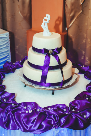 tiered: A traditional and decorative wedding cake at wedding reception. three tiered blue and white wedding cake with confectionery roses Stock Photo