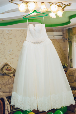 luster: wedding dress hanging on luster at hotel room. Flounces of delicate textile of wedding dress. Stock Photo